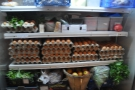 The long corridor is stacked full of produce for sale, like these eggs.