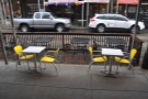 The two tables on the sidewalk are sheltered from the rain. The rest, however, are not...