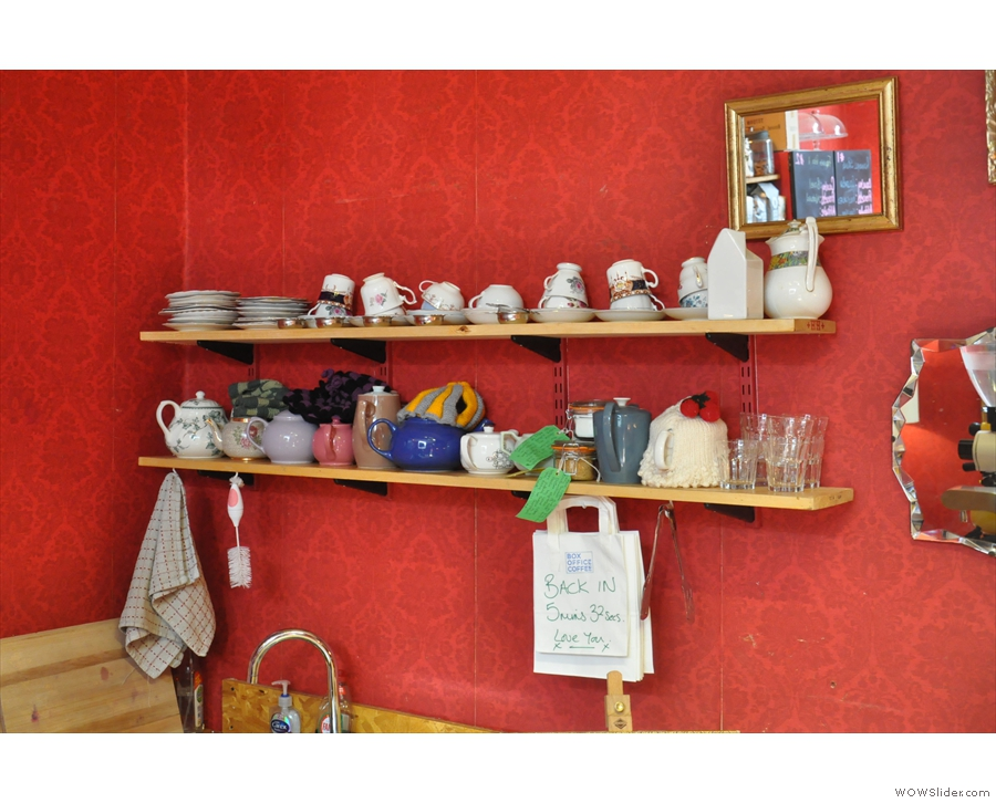 Meanwhile, over the sink in the corner, there are teapots and tea cups.