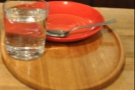 A saucer and its glass of water wait on the tray for the coffee