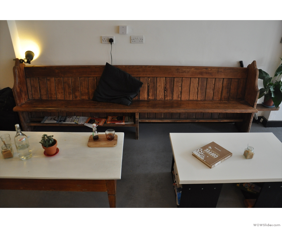 Opposite is an old church pew, with a pair of coffee tables & a neat magazine rack underneath.
