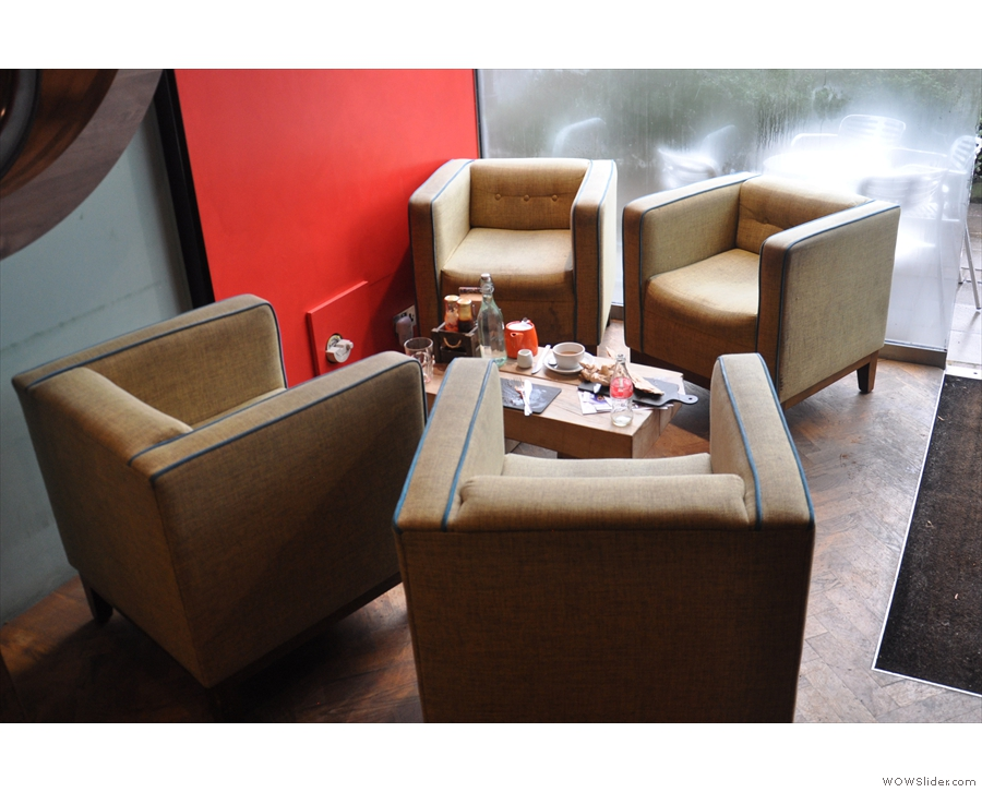 Stepping inside, these four comfy armchairs occupy the window to the right...