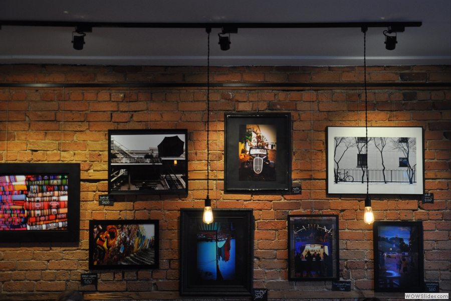 The wall opposite the counter is hung with works of art...