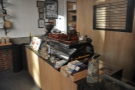 The counter is opposite the door, the espresso machine at the left-hand end.