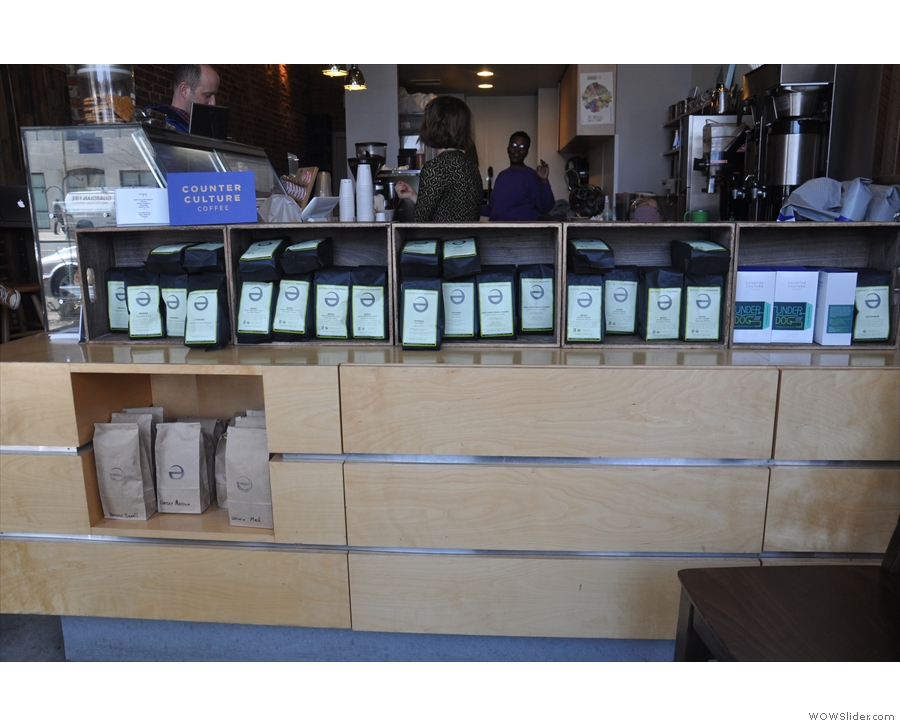 The retail section runs along the front of the counter, in the shape of bags of coffee for sale.
