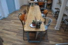 ...dominated by a long, thin communal table down the room's spine, another table beyond.