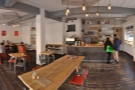 A panoramic view from just inside the door, counter ahead, seating to the left.