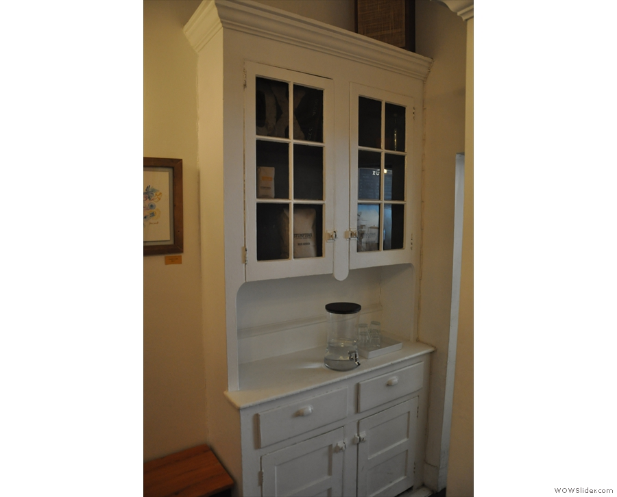 Returning to the back room, this lovely old cabinet is used as a water station & coffee store.
