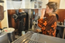 The barista checks her work (the coffee had only been cupped the day before).
