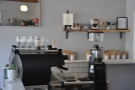 The view of the espresso machine from the stools at the right-hand end of the counter.