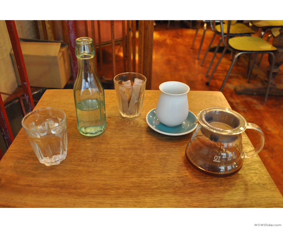 The coffee is served in a carafe, with a handleless cup. Plus a bottle of water.