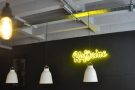 The (very prominent) Kaffeine logo in yellow neon is to the right, behind the counter.