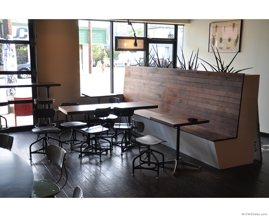 These tables line the bench seat, which acts as the divider between coffee shop & entrance.