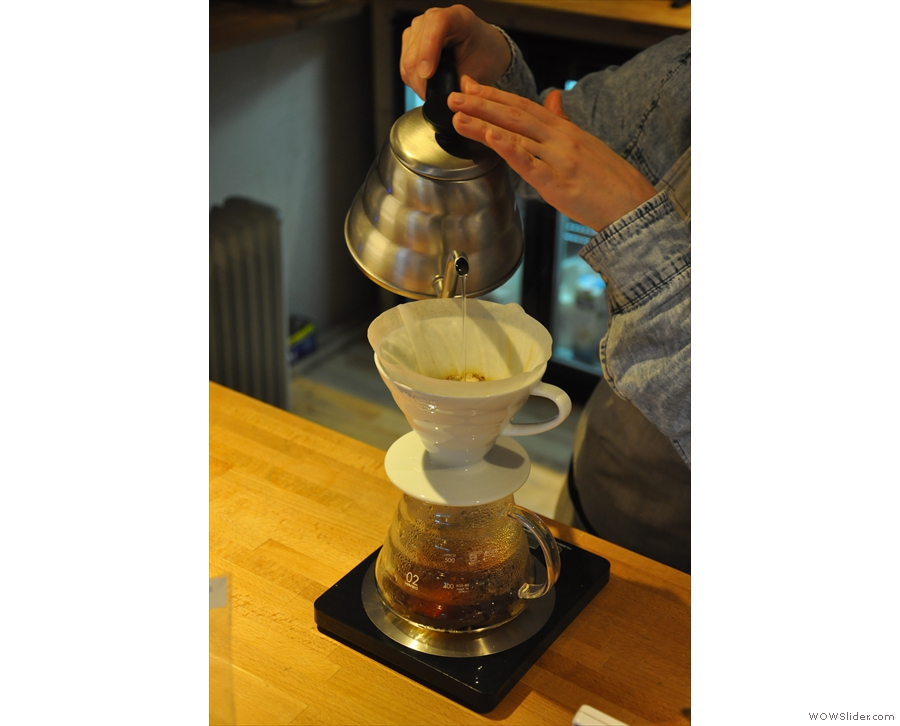 After letting the coffee bloom, she tops up the V60...