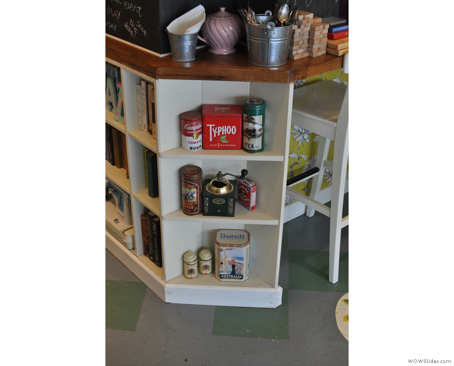 The counter is full of little bits and pieces like these shelves with their little coffee grinder.